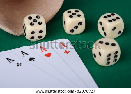 Closeup of four aces and four dices on green background