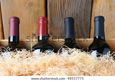 Closeup of four different wine bottles in a wooden crate with straw packing material. Stock photo ©