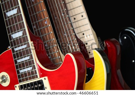Closeup of four electric guitars isolated over a black background.