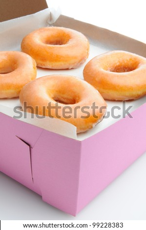 Closeup of four glazed donuts in a pink bakery box. Vertical format with a white background.