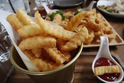 Closeup of frenchfries in a small bowl with ketchup as dip sauce. Frenchfries appetizer on the wooden tray.