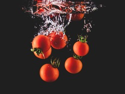 Closeup of fresh and health cherry tomatoes falling into clear water with big splash on black background. Group of fresh tomatoes falling into water with splash. Red tomato drop in water with bubble