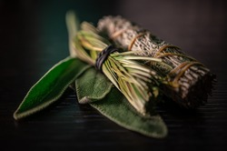 Closeup of Fresh & Dried Sage Native American Smudging Wiccan Bundles With Braided Sweet Grass Herbs On A Black Wooden Table Surface