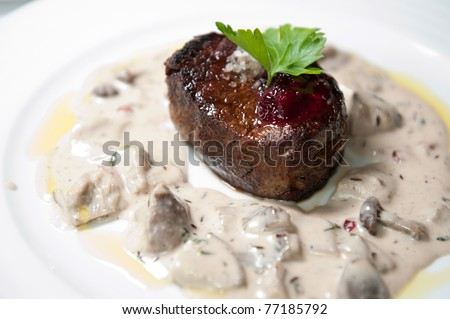 closeup of fresh grilled beef steak with cream mushroom sauce on white plate