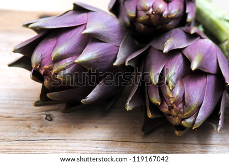 Closeup of fresh purple artichokes in rustic white wood background.Healthy eating, healthy lifestyles, natural bio food concept