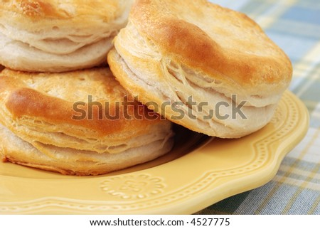 closeup of freshly baked biscuits on yellow ceramic plate with blue and yellow plaid tablecloth