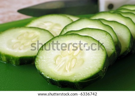 closeup of freshly sliced cucumbers on a green cutting board with knife visible in the background