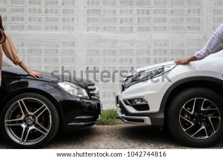Closeup of front side of black car with woman and white car with man, parking in the opposite direction with white wall background. #1042744816