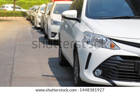 Closeup of front side of white car with  other cars parking in parking lot beside the street in bright sunny day. The mean of simply transportation in modern world. #1448381927