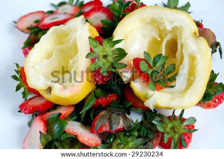 closeup of fruits (lemons and strawberries) scraps on a table.