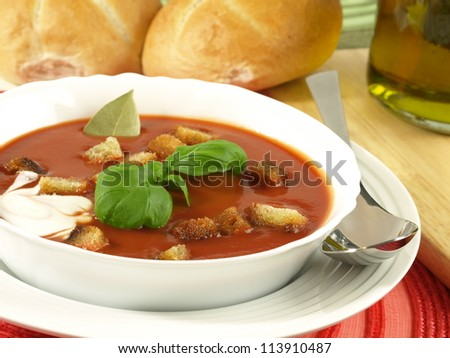 Closeup of garnished tomato soup with croutons and rolls in a background