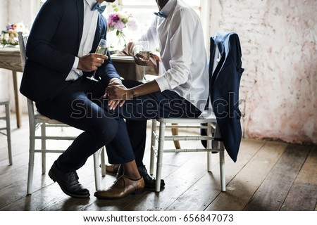 Closeup of Gay Couple Holding Hands Sitting Together