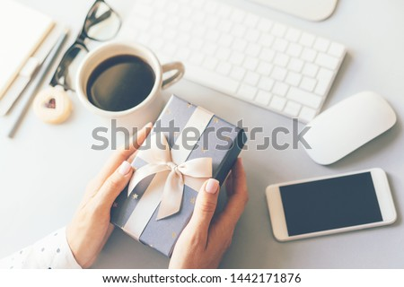 Closeup of gift box in female hands at workplace, coffee break at workspace, door-to-door delivery, Christmas or Valentine's day concept, corporate birthday party, mother's and women's day.