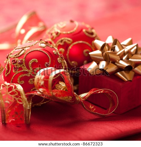 Closeup of gift box with golden bow and red christmas balls
