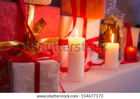 Closeup of gifts near a Christmas tree in the candlelight
