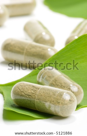 Closeup of Ginkgo Biloba extract pills and fresh Ginkgo Biloba leaves best suited for alternative medicine ads