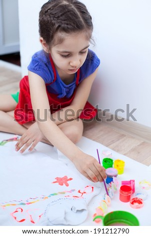 Closeup of girl child baby painting white blouse on the floor.  Acrylic paint and brushes for textile decoration. Baby\'s art.