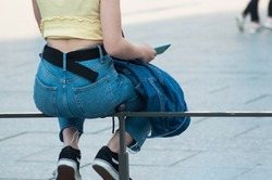 closeup of girl sitting on metallic fence wearing blue jeans  taking smartphone in hand
