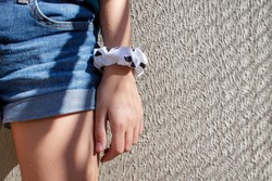 Closeup of girl wearing short jeans with scrunchies on her arm. Wall background. Textile scrunchies, hair elastic used as a fashion accessory.
