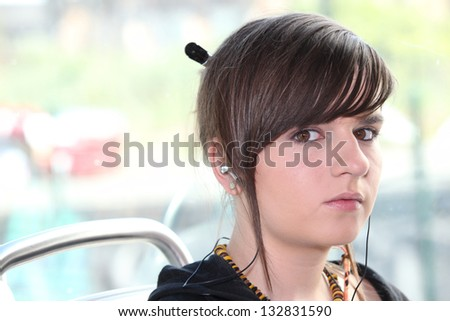 Closeup of girl with earphones sitting on a tram
