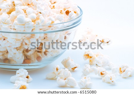 Closeup of glass bowl of popcorn with few peaces throw around