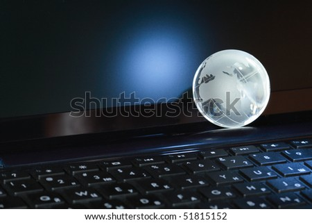 Closeup of glass globe lying on black computer keyboard