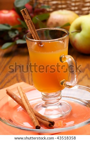 Closeup of glass of fresh pressed sweet cider, cinnamon sticks and apples crop