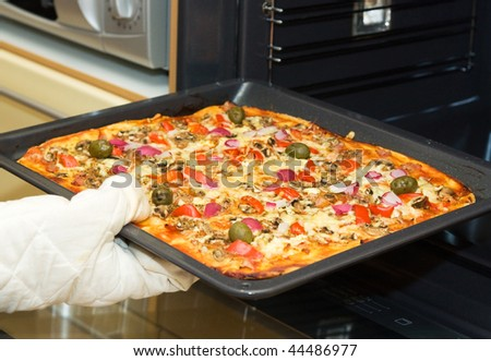 Closeup of gloved  hand taking a roasted pizza out of the oven