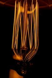 Closeup of glowing filament of Edison Bulb. Abstract light bulb filament macro shot. Decorative lighting
