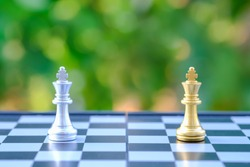 Closeup of gold and silver King chess pieces on chessboard with green nature background. Sport Boardgame and Compettition Concept.
