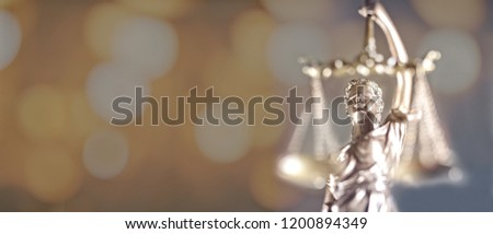 Closeup of golden lady Justice statue - focus on foreground with bokeh background #1200894349