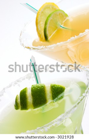 Closeup of Golden Margarita and Midori Margarita tequila cocktails garnished with lime and lemon wedges