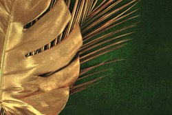 Closeup of golden palm and monstera leaves on abstract dark green textured background. Tropical conceptual elegant trendy summer background. Flat lay. Copy space.