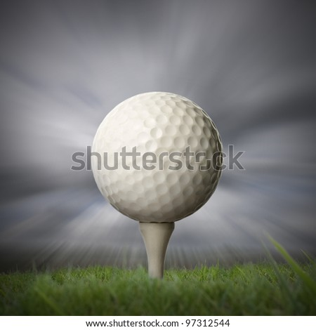closeup of golf ball on golf tee with stormy fast moving sky background