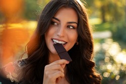 Closeup of gorgeous elegant young woman eating dark chocolate in the park
