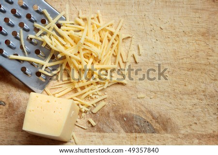 Closeup of grated cheese and grater lying on wooden cutting board