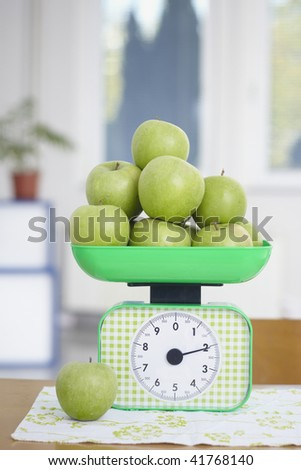 closeup of green apples on kitchen scale