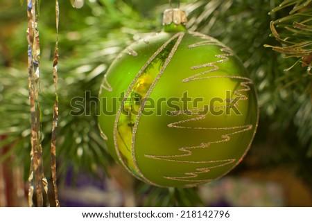 Closeup of green Christmas ball hanging on christmas tree