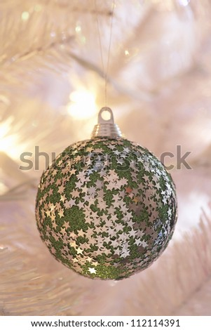 Closeup of green Christmas bauble hanging on tree - stock photo