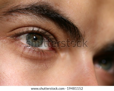 Closeup of green eyes of young man with a serious look on his face #19481152