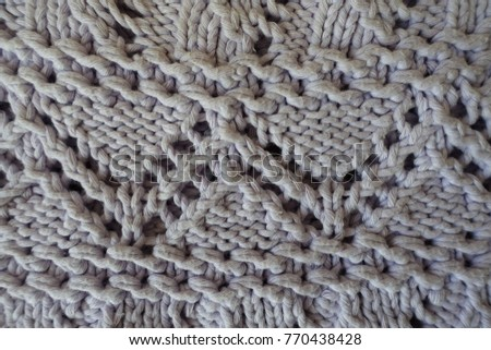 Closeup of grey handmade knitted fabric with zigzag pattern #770438428