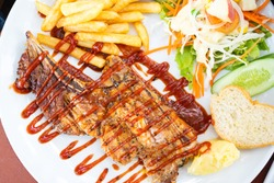 Closeup of grilled beef steak with salad on a plate, frenchfries and salad vegetables