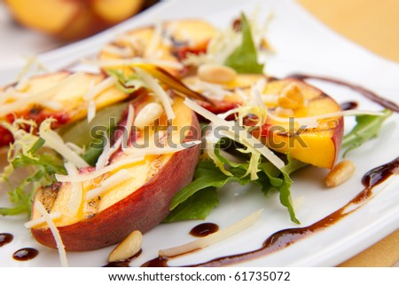 Closeup of grilled peaches salad with Parmesan cheese and roasted pine nuts. Balsamic vinegar sauce.