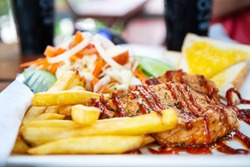 Closeup of grilled pork steak with salad on a plate, frenchfries and salad vegetables