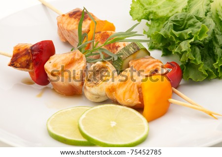 Closeup of grilled salmon and vegetable skewers with fresh tarragon and green salad