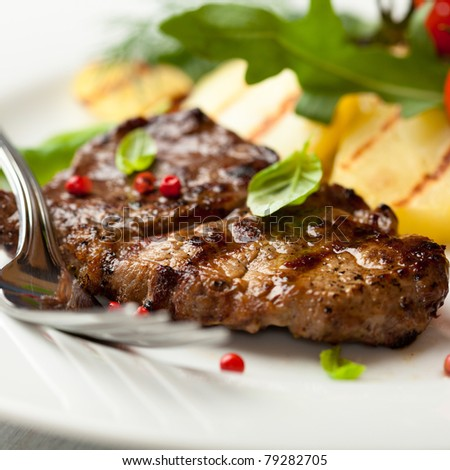 Closeup of grilled steak with pink pepper and basil