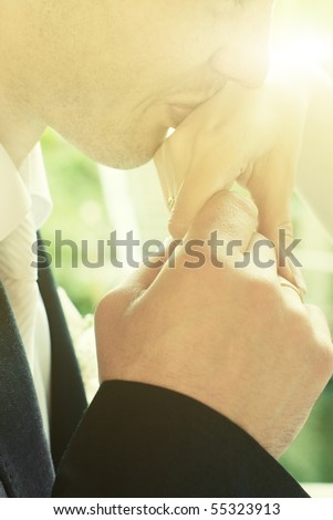 Closeup of groom kissing hand of bride with sunny flare and selective focus on rings