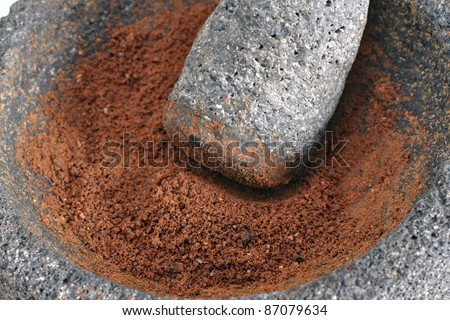 Closeup of ground cocoa beans in stone mortar