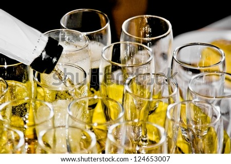 closeup of group of flutes of champagne on festive table and one is being filled