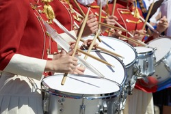 Closeup of group of girls of fans in red military uniform with drums. Support group on the team.